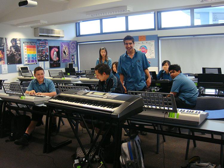 キーボードのある教室で談笑する学生たち